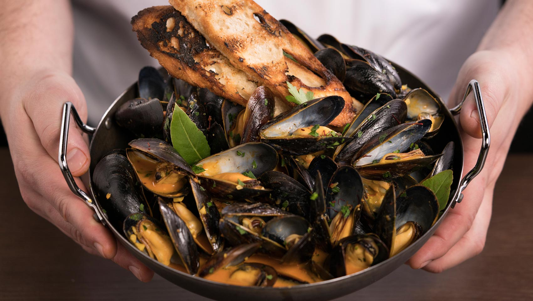 Hands holding a bowl of mussels