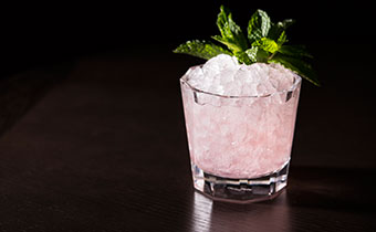 Pink cocktail with ice and mint leaf