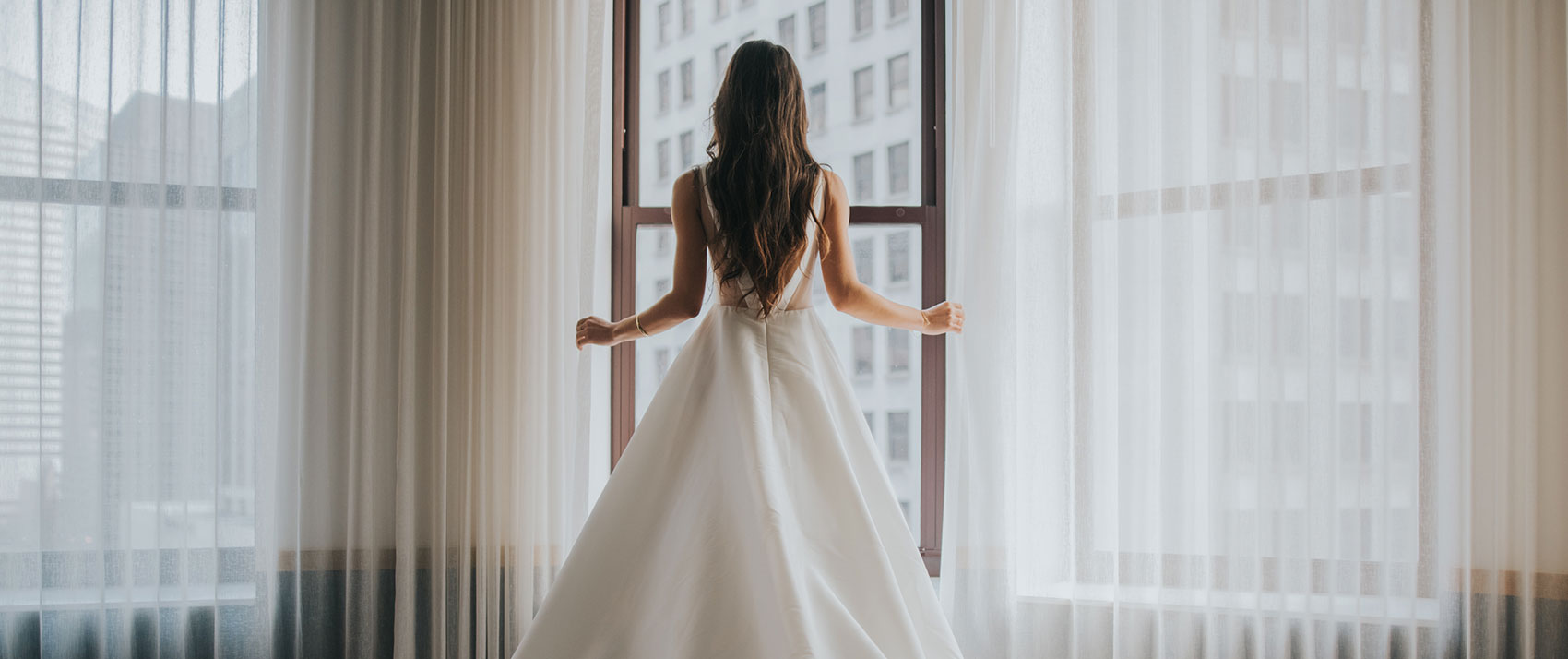 Vows There, Stay Here Brand Image. Bride standing in white wedding dress around window